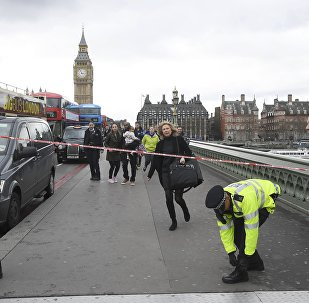 A woman ducks under a police tape after an incident on Westminster Bridge in London