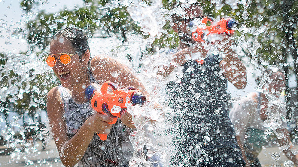People take part in a ten-minute flashmob on June 24, 2017 at a fountain in Lausanne, to cool off as heatwave scorches Europe.