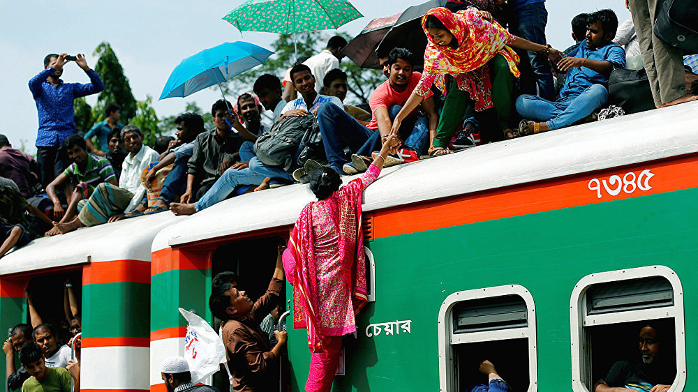 A woman helps another woman to get atop of an overcrowded passenger train as they travel home to celebrate Eid al-Fitr festival at a railway station in Dhaka