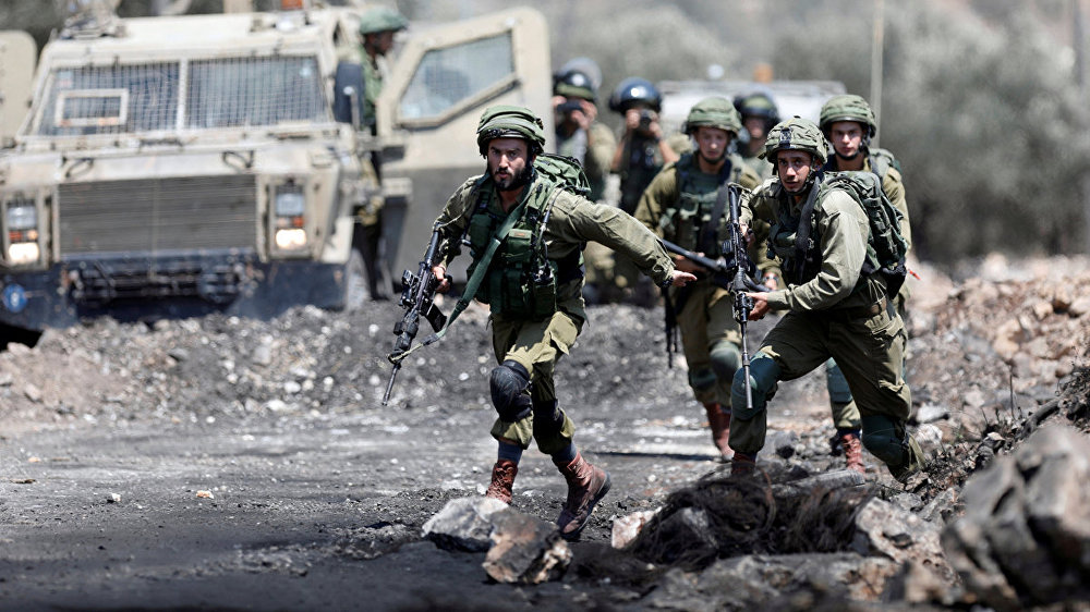 Israeli soldiers run during clashes with Palestinian protesters in the West Bank village of Kofr Qadom near Nablus