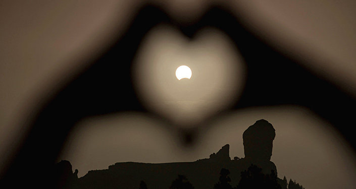 A woman makes a heart shape with her hands during a partial eclipse of the sun over the Roque Nublo mountain at the Canary Island of Gran Canaria
