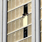 Workers board up a broken window at the Mandalay Bay hotel in Las Vegas