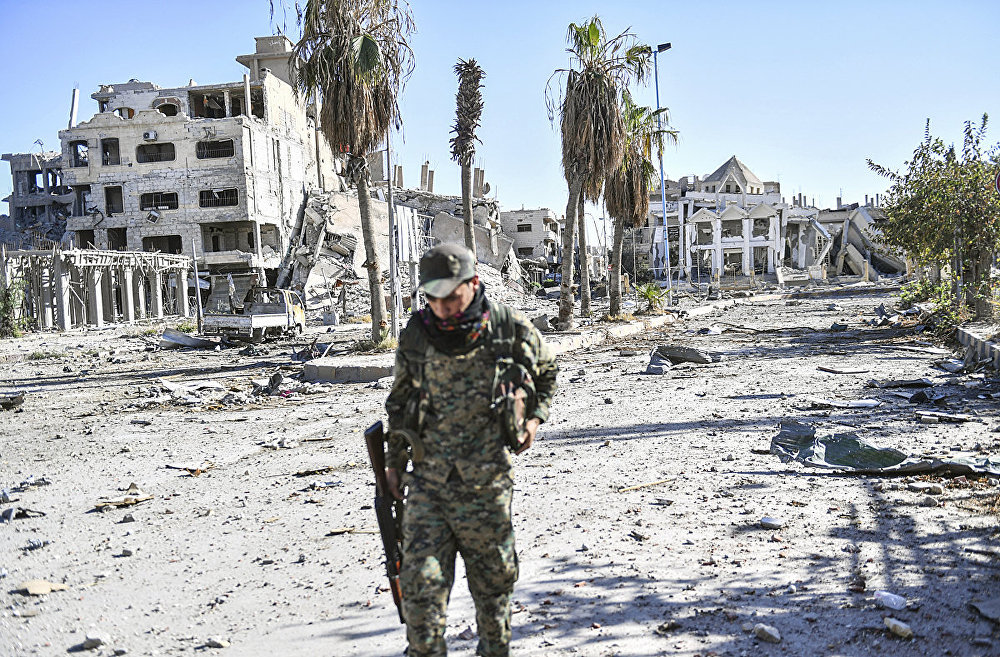 A member of the Syrian Democratic Forces (SDF) walks through a heavily damaged a street leading to an Armenian church in Raqa on October 18, 2017
