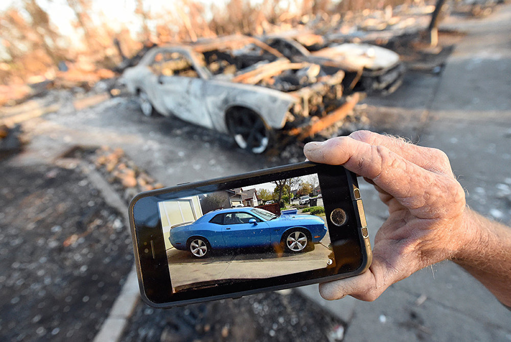 Car collector Gary Dower holds up a photo showing his 2010 Dodge Challenger Limited Edition SRT8 before it burned at his home in Santa Rosa, California on October 20, 2017