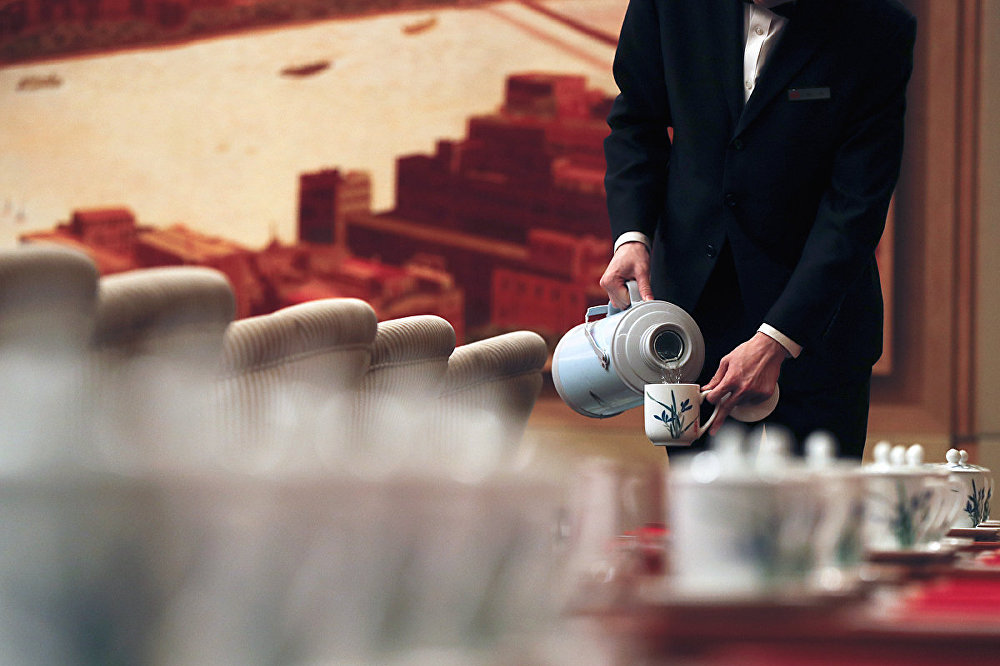 Hostesses fills tea cups for the Shanghai's delegates before a discussion group meeting on the sidelines of China's 19th Party Congress at the Great Hall of the People in Beijing, Thursday, Oct. 19, 2017.