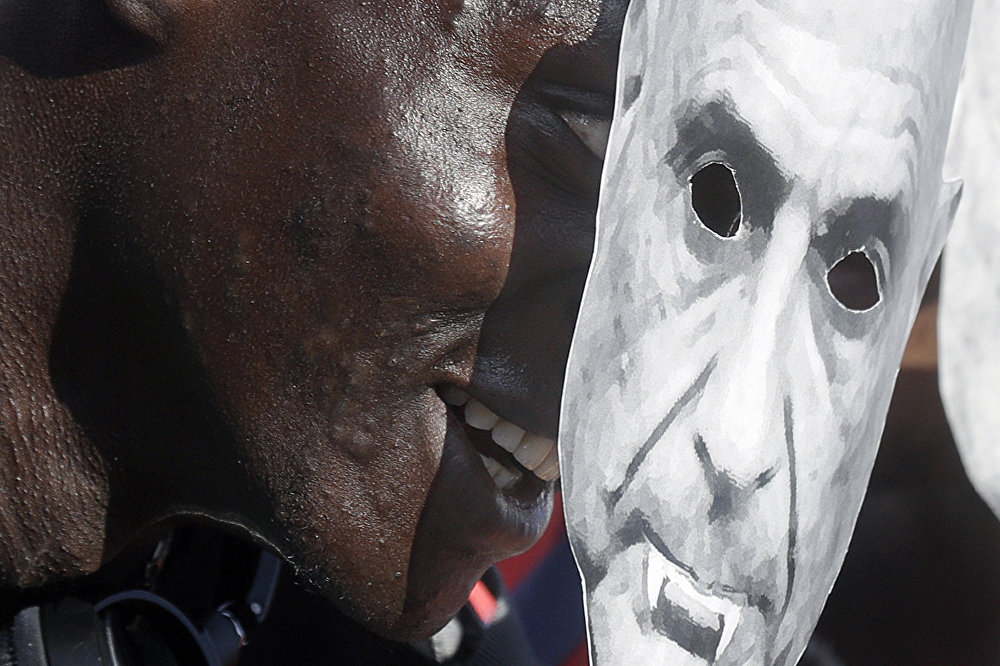 A demonstrator holds a mock mask depicting the Italian Interior Minister Marco Minniti as a Vampire during a pro-migrants and against racism demonstration, organized by a number of leftist organizations including labor unions, Amnesty International and MSF (Doctors Without Borders) in Rome, Saturday, Oct. 21, 2017