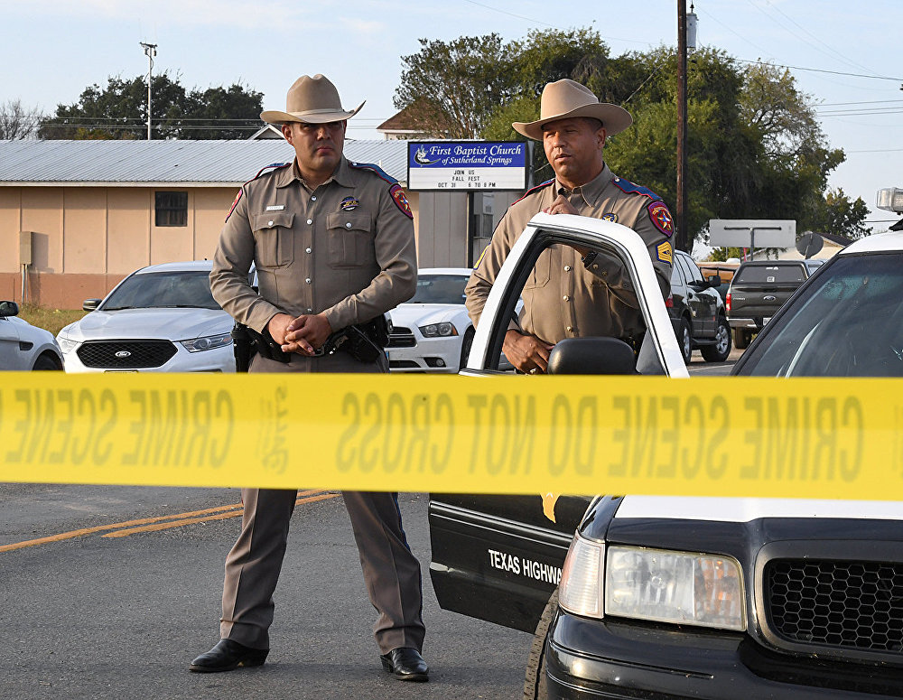 State troopers guard the entrance to the First Baptist Church (back) after a mass shooting that killed 26 people in Sutherland Springs, Texas on November 6, 2017. A gunman wearing all black armed with an assault rifle opened fire on a small-town Texas church during Sunday morning services, killing 26 people and wounding 20 more in the last mass shooting to shock the United States.
