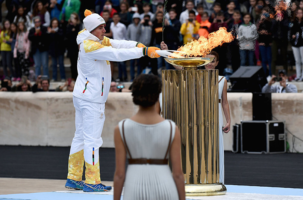 Greek Alpine skier Ioannis Proios (L) lights an Olympic torch from a cauldron at The Panathenaic Stadium in Athens on October 31, 2017, during the handover ceremony of the Olympic flame for the 2018 Winter Olympics in Pyeongchang, South Korea.
